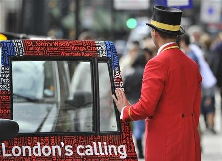 A doorman closes a taxi door outside a hotel in central London
