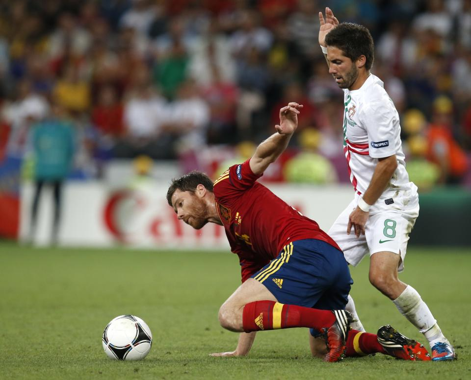 Spain's Xavi Hernandez, left, and Portugal's Joao Moutinho vie for the ball during the Euro 2012 soccer championship semifinal match between Spain and Portugal in Donetsk, Ukraine, Wednesday, June 27, 2012. (AP Photo/Armando Franca)