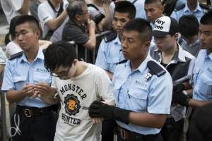 Protesters are taken away by police officers after staying overnight at Hong Kong's financial Central district