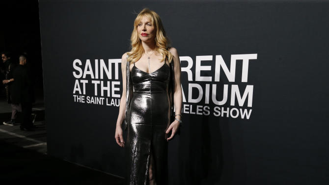 Singer Love poses as she arrives for the Saint Laurent fall collection fashion show at the Hollywood Palladium in Los Angeles