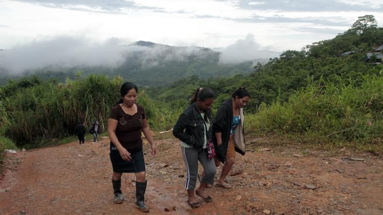 Relatives of missing miners walk near the site of a landslide at a gold mine, at the El Comal community in Bonanza