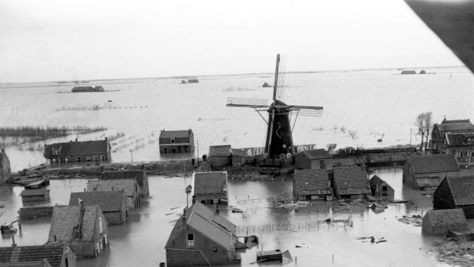 "FILE - This February 1953 file photo shows an aerial view of a windmill pump elevated above the floodwaters in the coastal village of Oude Tonge in The Netherlands. It took the collapse of dikes, drowning deaths of more than 1,800 people, and evacuation of another 100,000 in 1953 for the Dutch to say ""Never again!"" They have since constructed the world's sturdiest battery of dikes, dams and barriers. No disaster on that scale has happened since. (AP Photo/File)"