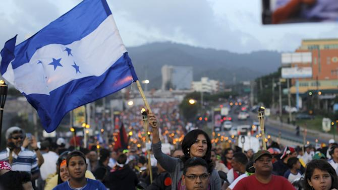 A woman holds a Honduras flag in a march demanding the resignation of Honduras' President Juan Hernandez in Tegucigalpa