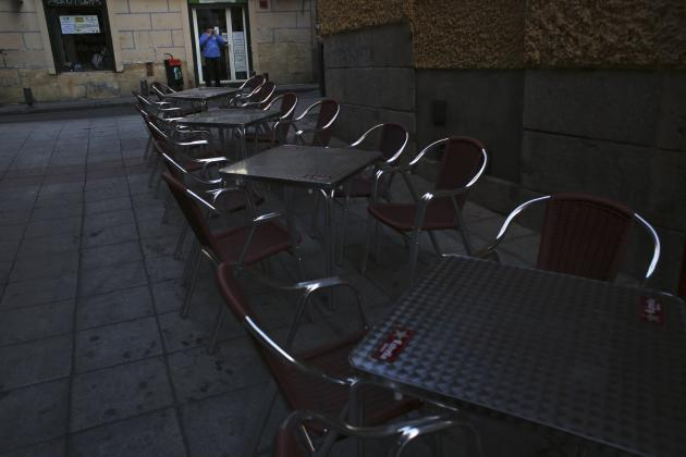 A man smokes next to empty restaurant tables in central Madrid