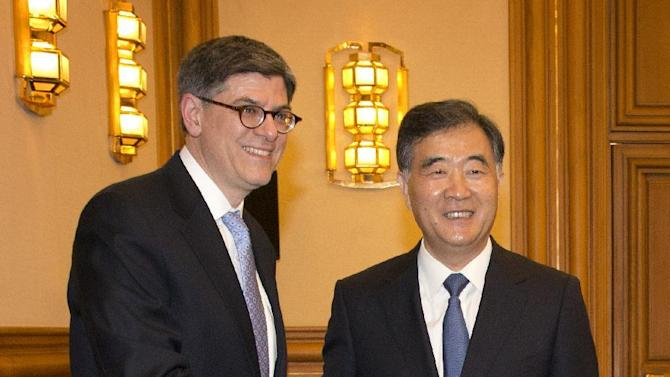 """U.S. Treasury Secretary Jacob Lew, left, shakes hands with Chinese Vice Premier Wang Yang as he arrives for a meeting at the Zhongnanhai Leadership Compound in Beijing Monday, March 30, 2015. In the meeting Lew expressed """"deep concern"""" about the curbs in proposed bank security and anti-terrorism rules. (AP Photo/Mark Schiefelbein, Pool)"""