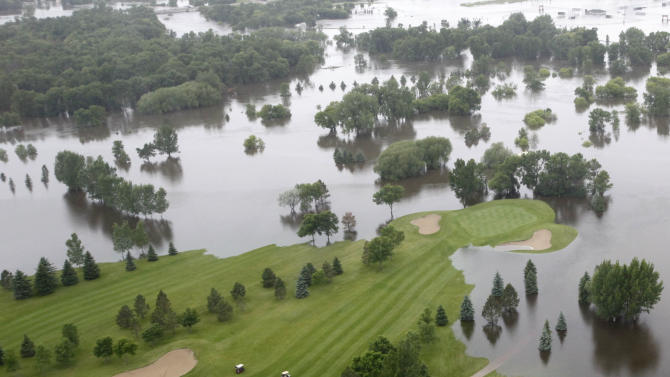 In this aerial photo, patrons of the Souris Valley Golf Course, center, continue to play the shortened course as flood waters from the Souris River continue to rise Friday, June 24, 2011 in Minot, N.D. North Dakota Gov. Jack Dalrymple says the Souris River is flowing over most levees in Minot as it surges past a 130-year-old record level.   (AP Photo/Charles Rex Arbogast)
