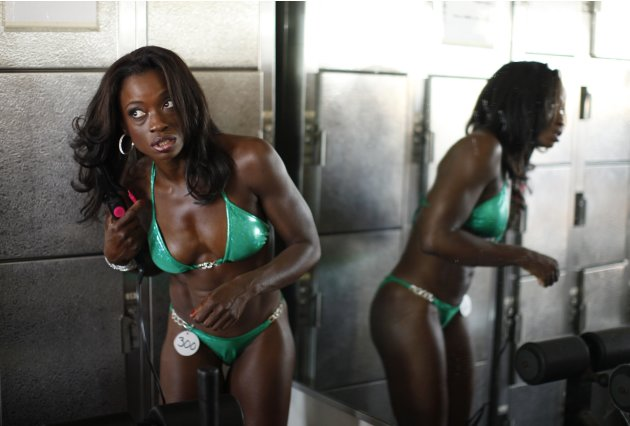 A woman styles her hair at the Muscle Beach Independence Day bodybuilding contest on Venice Beach in Los Angeles, California