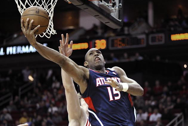 Atlanta Hawks' Al Horford (15) hooks a shot in front of Houston Rockets' Omer Asik in the first half of an NBA basketball game Wednesday, Nov. 27, 2013, in Houston