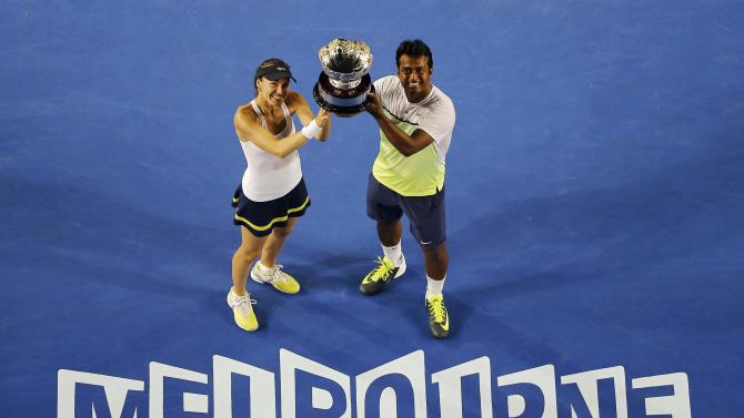Hingis of Switzerland and Paes of India pose with their trophy after defeating Mladenovic of France and Nestor of Canada to win their mixed doubles final match at the Australian Open 2015 tennis tournament in Melbourne