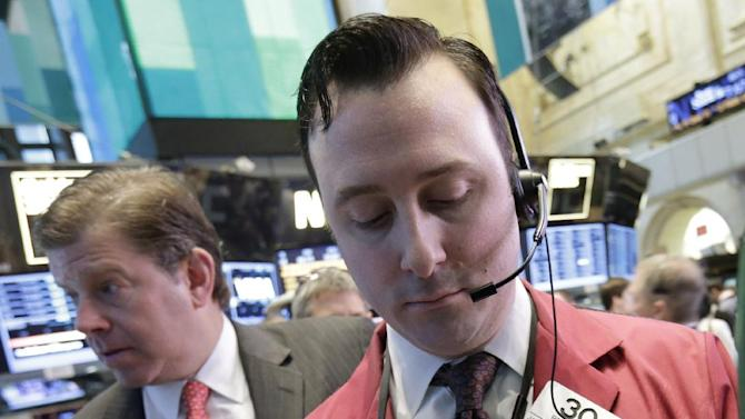Trader Brandon Barb, right, works on the floor of the New York Stock Exchange Wednesday, Feb. 6, 2013. Strong earnings reports from media giants Disney and Time Warner aren't impressing investors in early trading, and major U.S. market indexes are opening lower. (AP Photo/Richard Drew)