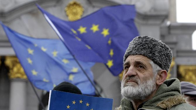 A demonstrator holds European Union flag during a protest in support of Ukraine's integration with the European Union in the center of of Kiev, Ukraine, Friday, Nov. 29, 2013. The European Union extended its geopolitical reach eastward on Friday by sealing association agreements with Georgia and Moldova, but blamed Russia for missing out on a landmark deal with Ukraine. In center of the small flag in the foreground is a Crimean Tatar symbol on the EU flag. (AP Photo/Sergei Chuzavkov)
