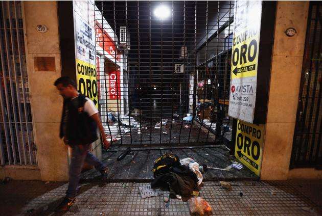 A plain-clothes policeman walks away from looted gallery store after riots broke out during celebrations of Boca Juniors Fan Day in Buenos Aires