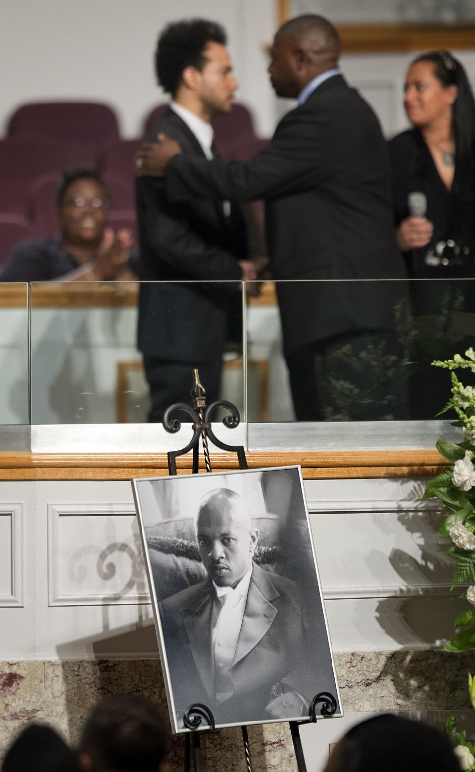 A photo of Chris Kelly of the rap duo Kris Kross is displayed as fellow Kris Kross member Chris Smith, top left, is comforted during his funeral service, Thursday, May 9, 2013, in Atlanta. The 34-year-old Kelly was found dead May 1 of a suspected drug overdose.  (AP Photo/David Goldman)