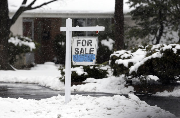 In this Wednesday, Feb. 27, 2013 photo, a for sale sign hangs outside a home in Glenview, Ill. Average U.S. rates on fixed mortgages were little changed the first week of March, hovering near historic