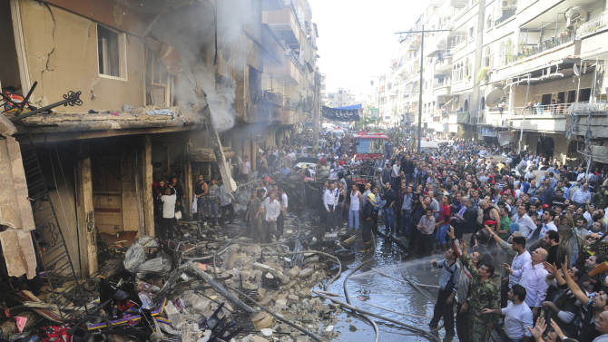 In this photo provided by the Syrian official news agency SANA, Syrian citizens gather in front of a damaged building that destroyed by a car bomb, at Jaramana neighborhood, in Damascus, Syria, Monday, Oct. 29, 2012. A Syrian government official says a car bomb in a Damascus suburb has killed 10 people. The official said the blast on Monday in Jaramana also wounded 41 people and caused heavy damage. He spoke on condition of anonymity because he was not authorized to speak to the media. (AP Photo/SANA)