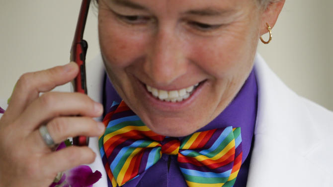 Faith Kassan, 46, wears a rainbow-colored bow tie while talking on the phone before her wedding ceremony in West Hollywood, Calif., Monday, July 1, 2013. The city of West Hollywood is offering civil marriage ceremonies Monday for same-sex couples free of charge. (AP Photo/Jae C. Hong)