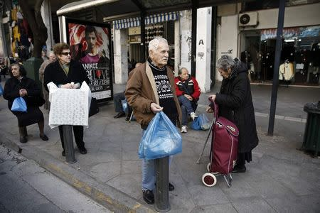 People carrying goods wait at a bus stop in Athens' commercial district