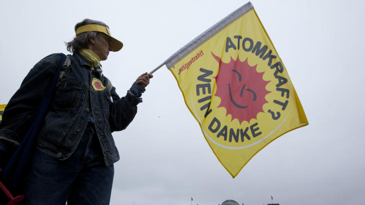 An anti-nuclear protester holds a flag reading ' Nuclear power - no thanks' as she demonstrates in front of the German parliament the Reichstag building in Berlin, Germany, Thursday, June 30, 2011. In a final debate German lawmakers are preparing to vote on the government's plan to shut down the country's nuclear power plants by 2022. (AP Photo/Markus Schreiber)
