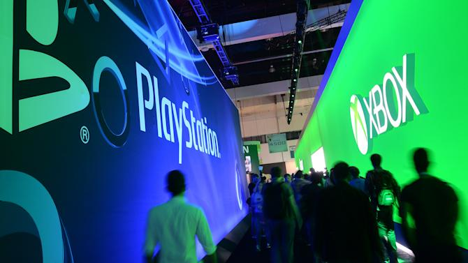 Attendees walk between signs for Sony PlayStation and Microsoft's XBox on the first day of the Electronic Entertainment Expo in Los Angeles, on June 11, 2013
