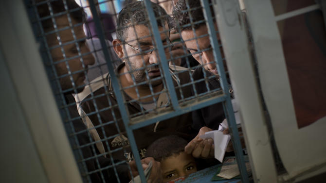 Palestinians present their identification as they wait to receive food aid at a UN distribution center in Shati refugee camp, Gaza City, Monday, Nov. 19, 2012. Exchange of fire between Israel and Gaza militants continued for the sixth day on Monday. (AP Photo/Bernat Armangue)