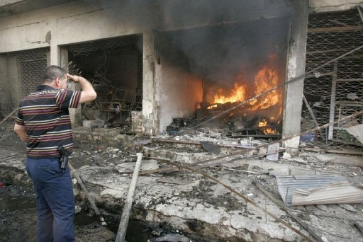 An Iraqi man looks at a fire inside a store following a car bomb that exploded in the northern city of Kirkuk