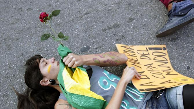 A protester lies on the ground in front of a police line in Rio de Janeiro, Brazil, Sunday, June 16, 2013. Brazilian police dispersed a small protest against a public transport fare hike that broke out in front of Rio de Janeiro's Maracana stadium ahead of the Mexico-Italy soccer match during the Confederations Cup. (AP Photo/Bruno Magalhaes)