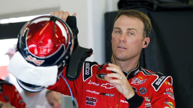 Kevin Harvick puts on his helmet during practice for the NASCAR Sprint Cup Series Coke Zero 400 auto race at Daytona International Speedway, Thursday, July 5, 2012, in Daytona Beach, Fla. (AP Photo/Terry Renna)