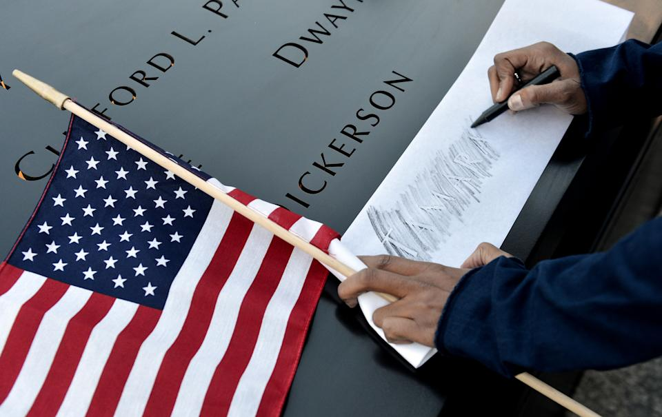 Alicia Watkins, of Washington, DC, makes a rubbing of a friend's name at the South Pool of the World Trade Center Memorial during the 11th anniversary observance at the site in New York, Tuesday Sept. 11, 2012. (AP Photo/Justin Lane, EPA, Pool)