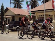 Cyclists riding past Indonesia's police post in Motain, a border between East Timor and Indonesia in September 13. This year is the fourth Tour de Timor, but the first time the six-day mountain bike race has crossed international borders, weaving through Indonesian West Timor into the mountainous enclave of Oecusse