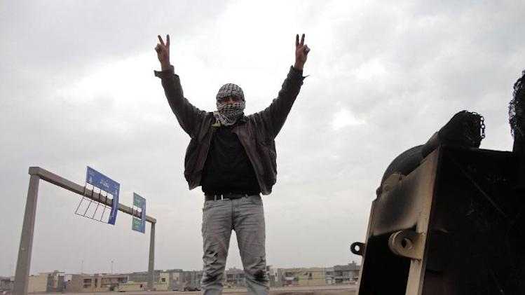 A man flashes the V-sign for victory as he stand on top of a burnt-out lorry on the side of the main highway leading west out of Baghdad to Fallujah, on January 5, 2014