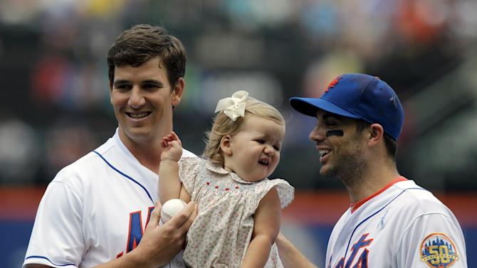 New York Giants quarterback Eli Manning, left, holds daughter Ava as he stands with New York Mets third baseman David Wright after Wright caught his ceremonial first pitch before a baseball game against the Cincinnati Reds at Citi Field in New York, Sunday, June 17, 2012. (AP Photo/Kathy Willens)