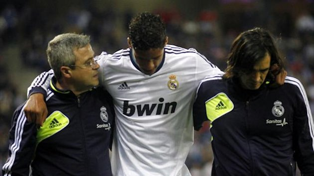 Real Madrid's Raphael Varane (C) leaves the pitch injured,