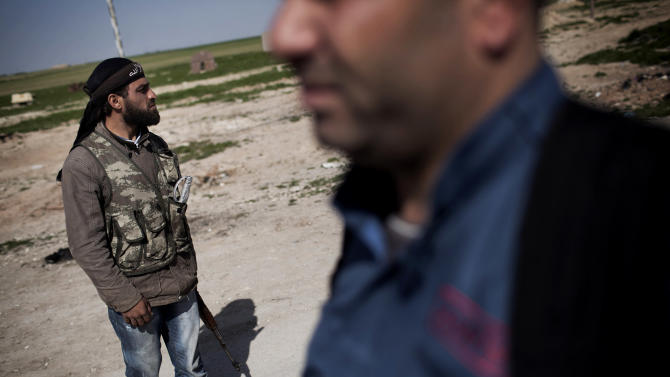 Members of the Kurdish Popular Protection Units and Free Syrian Army fighters stand guard at a check point in Ras al-Ayn, Syria, Wednesday, Feb. 27, 2013. The U.N. says more than 70,000 people have been killed since Syria's civil war started in March 2011. (AP Photo/Manu Brabo)