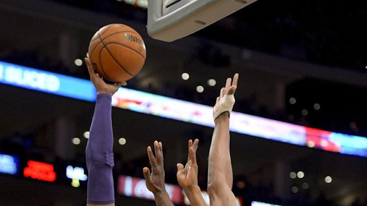Los Angeles Lakers guard Kobe Bryant (24) shoots over Boston Celtics forward Chris Wilcox, right, and guard Jason Terry (4) during the first half of their NBA basketball game, Wednesday, Feb. 20, 2013, in Los Angeles. (AP Photo/Mark J. Terrill)