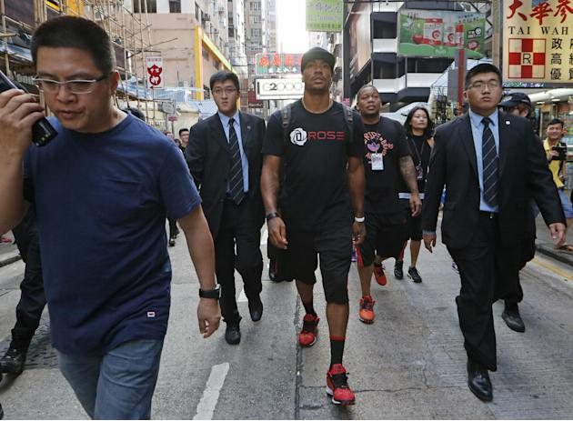 NBA star Derrick Rose of Chicago Bulls, center, walks in a shopping district in Hong Kong after attending a promotional event as part of his Asia tour Friday, Sept. 13, 2013. Rose will visit Manila, t