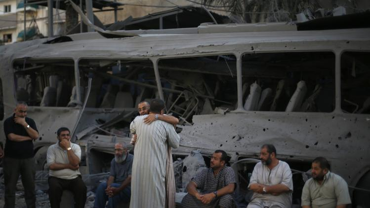 Palestinians react in front of a bus that witnesses said was destroyed during an Israeli airstrike in Gaza City
