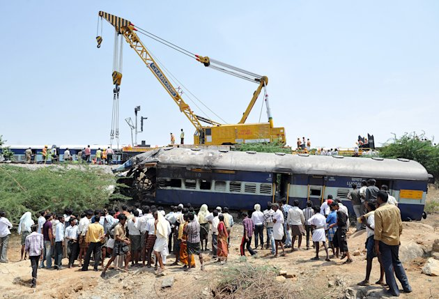 Local villagers watch as a heavy duty railway crane lifts the mangled remains of a coach of the Bangalore-bound Hampi Express after it collided with a stationary goods train near Penneconda town in An