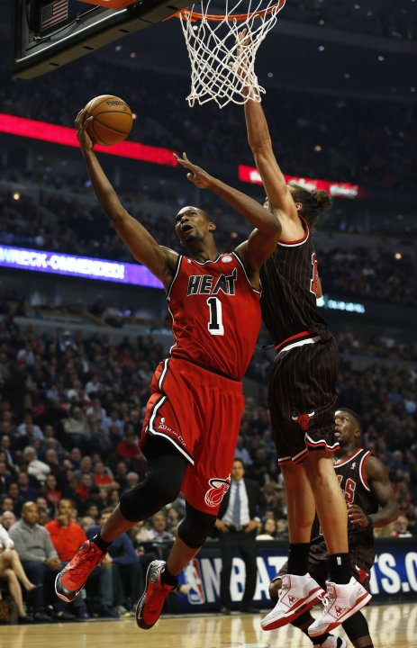 Miami Heat's Bosh goes to the basket against Chicago Bulls' Noah during the first half of their NBA game in Chicago