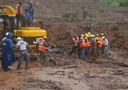 NDRF personnel carry the body of a victim from the site of a landslide at Malin village