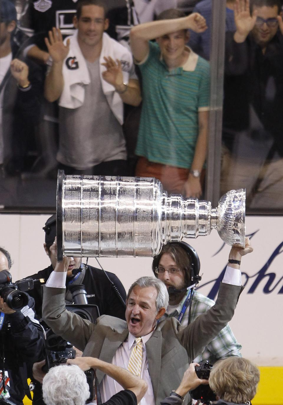 Los Angeles Kings coach Darryl Sutter hoists the Stanley Cup after beating the New Jersey Devils 6-1 during Game 6 of the NHL hockey Stanley Cup finals, Monday, June 11, 2012, in Los Angeles.  (AP Photo/Jae C. Hong)