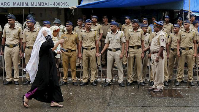 Indian policemen stand guard as women walk pass near the residence of Memon in Mumbai