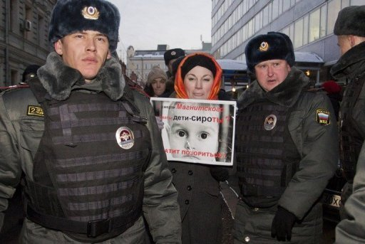 "<p>Russian police detain a protester holding a poster which reads: ""Do orphans guilty of Sergei Magnitsky's death? Stop the shame!"" just outside the parliament in Moscow on December 19, 2012.</p>"