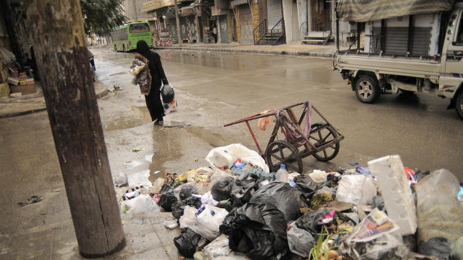 In this Saturday, Nov. 10, 2012 photo, a women passes accumulated garbage in the Al-Bohout area of Aleppo, Syria. Due the heavy fighting and shelling, the garbage collection system collapsed weeks ago. (AP Photo/Mónica G. Prieto)