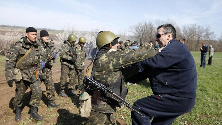 A Ukrainian soldier clashes with a pro-Russia protester in the field near Kramatorsk