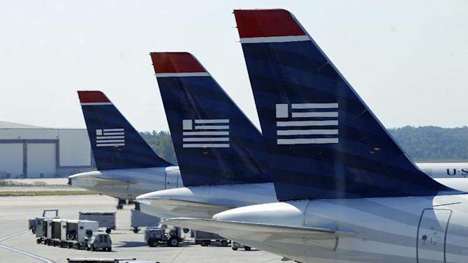 In this Thursday, Sept. 27, 2012, photo, US Airways jets are parked at their gates at the Charlotte/Douglas International airport in Charlotte, N.C. US Airways reports quarterly earnings on Wednesday, July 24, 2013. (AP Photo/Chuck Burton)