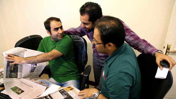 Iranian journalists, Soroush Farhadian, left, Mojtaba Fathi, right, and photographer Hadi Yazdani, confer about published pictures of former President Akbar Hashemi Rafsanjani, a hopeful for the upcoming presidential election, in several newspapers, at their pro-reform Bahar newspaper, in Tehran Iran, on Sunday, May 12, 2013.  Rafsanjani's made a last minute surprise decision on Saturday to enter Iran's presidential election process, which now includes more than 680 hopefuls and will culminate June 14 with just a handful of names on the ballot to succeed Mahmoud Ahmadinejad. In one of his first statements since joining the race, Rafsanjani spoke in general terms Sunday of seeking a new ``economic and political'' rebirth in a time of ``foreign threats and sanctions.'' (AP Photo/Vahid Salemi)