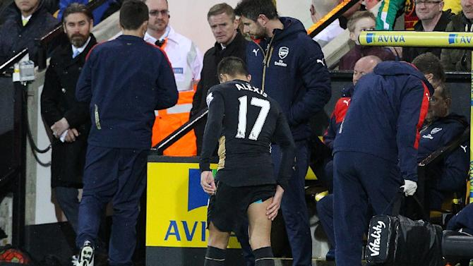 Arsenal's Chilean striker Alexis Sanchez limps off the pitch holding his leg during the English Premier League football match between Norwich City and Arsenal at Carrow Road in Norwich, eastern England on November 29, 2015