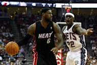LeBron James (L) of the Miami Heat looks to drive the ball past New Jersey Nets' Anthony Morrow on April 16. Miami rallied late behind James to defeat host New Jersey 101-98