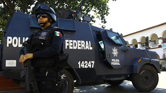 Mexican federal police stand guard in Michoacan State, Mexico, on January 14, 2014, where authorities have found nearly 600 people, most of them children, living in squalid conditions amid rats and insects in a residential facility