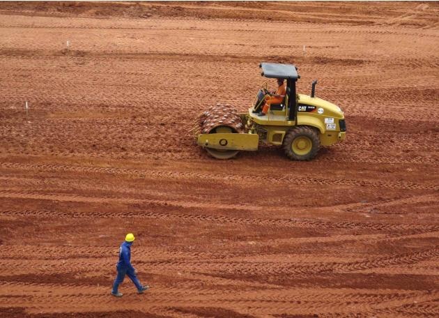 A workman rolls out dirt for the pitch inside the Arena da Baixada stadium as work continues in preparation for the 2014 FIFA World Cup soccer championship in Curitiba